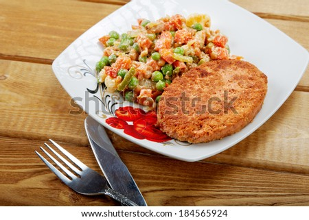 Fish cutlet with a vegetable garnish on a table - stock photo