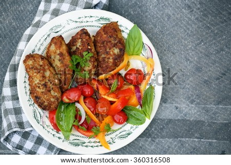 Fish cutlets with a salad of cherry tomatoes, food top view - stock photo