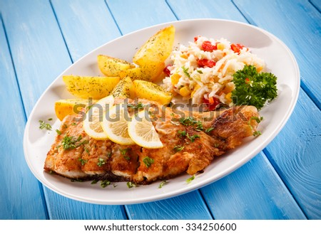 Fish dish - fried fish fillet baked potatoes and vegetables - stock photo