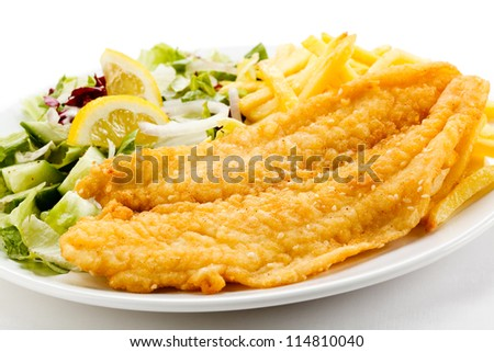 Fish dish - fried fish fillet, French fries with vegetables - stock photo