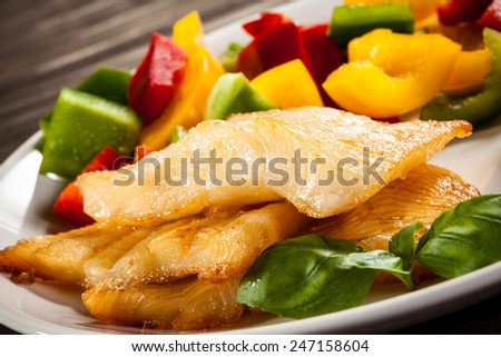Fish dish - fried halibut and vegetables - stock photo