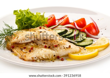 Fish dish - roast cod fillet and vegetables - stock photo