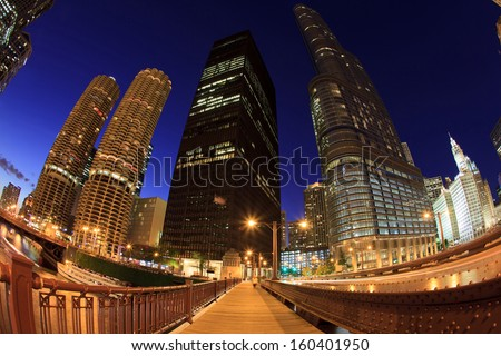 Fish eye cityscape of the downtown Chicago Riverwalk in the early evening with tall skyscrapers and historic architecture. - stock photo