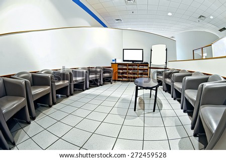 Fish Eye View Of Empty Chairs In Waiting Room With Blank Television Screen For Copy Space - stock photo