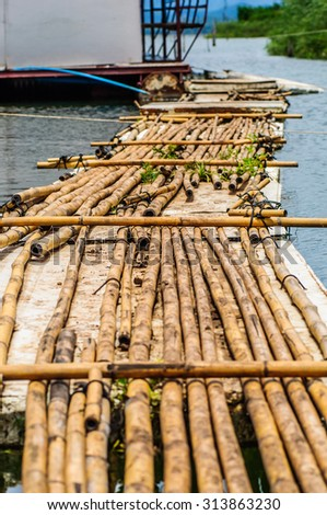 Fish farms with blue net and bamboo pathway - stock photo