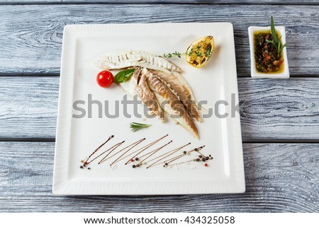 Fish fillet on a plate. Fish with lemon and tomato. Tasty dorado fish with spices. Natural meal and herbal sauce. - stock photo