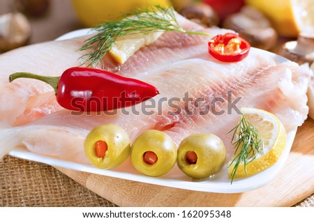 Fish fillet, stuffed olives, lemon and herbs on cutting board. - stock photo