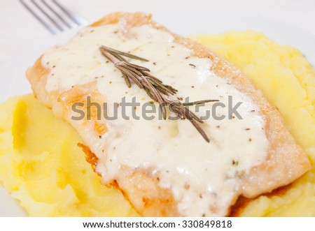 fish fillet under cheese with mashed potatoes - stock photo