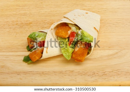 Fish finger and salad tortilla wraps on a wooden board - stock photo