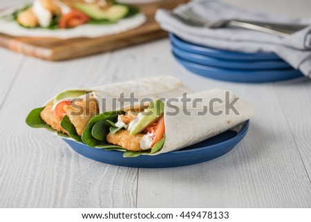 Fish finger wraps with avocado and tomato serves on blue plate