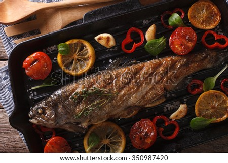 Fish food: trout with vegetables on a grill pan close-up on the table. horizontal view from above - stock photo