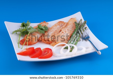 Fish fried in pastry with asparagus and tomatoes against a blue background