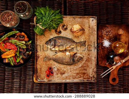 Fish gilthead (sea) Bram ideal for diet and slimming people,Grilled mushrooms and peppers lay in a deep cast iron cookware - stock photo