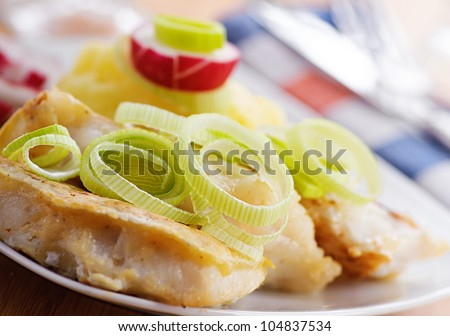 Fish in batter to plate and cherry on wooden table. - stock photo