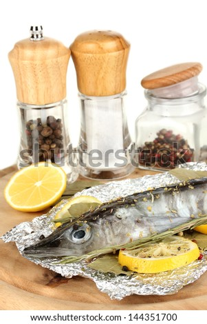 Fish in foil with herbs and lemon on board isolated on white - stock photo
