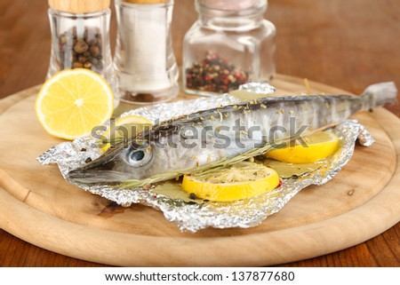 Fish in foil with herbs and lemon on board on wooden table close-up - stock photo