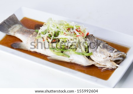 Fish in soy sauce, served on white plate  - stock photo