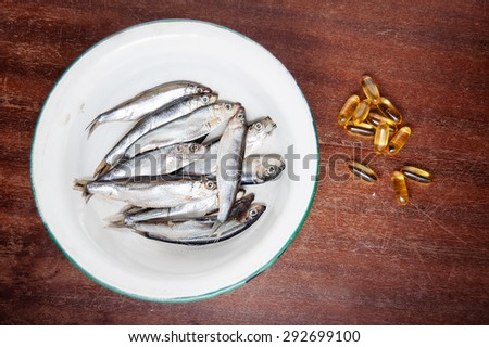 fish in white enamel bowl iron and vitamins omega three on a brown wooden table - stock photo