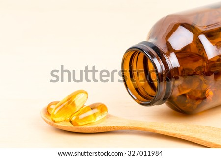 Fish oil capsule food supplement in wooden spoon - stock photo