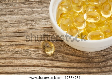 fish oil capsules - a small ceramic bowl on a grained wood - stock photo