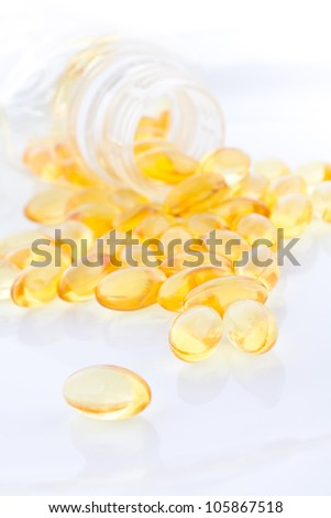 Fish oil capsules and container - stock photo