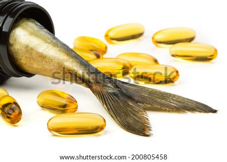 Fish oil capsules and fish tail in brown jar - stock photo