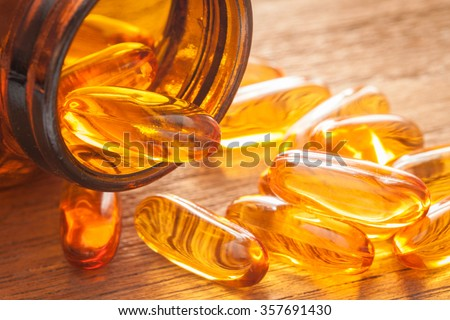 Fish oil capsules coming out of glass bottle on wooden texture, close up shot - stock photo