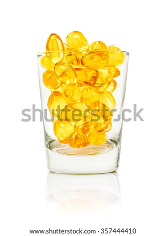 fish oil capsules in glass isolated on white background with clipping path - stock photo