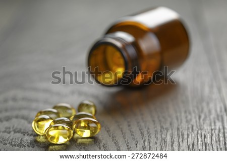 fish oil capsules with bottle on wooden table - stock photo