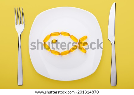 fish oil soft gels lying on white porcelain plate in the form of fish (yellow background) - stock photo