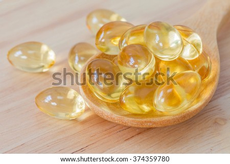 Fish oil supplement capsule, source of omega-3 on wooden spoon and natural wooden background - stock photo