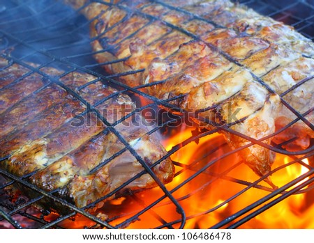 Fish on the grill. Summer barbecue concept. Close up with shallow DOF. - stock photo