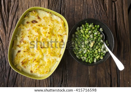 Fish pie topped with mashed potato and garden peas. Sitting on a rustic wooden table. - stock photo