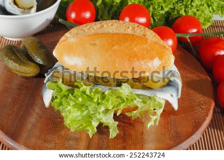 Fish rolls with sour herring, pickled herring, garnished with lettuce, tomato and pickles on a wooden board - stock photo