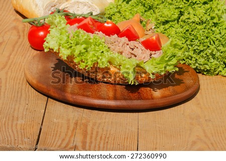 Fish rolls with tuna fillet garnished with lettuce, tomato, onion and pickles on a wooden board - stock photo