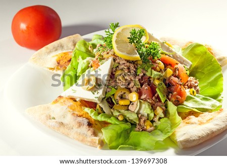 Fish salad on white plate, studio isolated.
