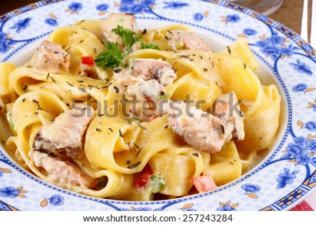Fish salmon fillet and tagliatelle noodle with cream sauce, close up - stock photo