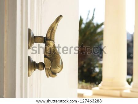 Fish shaped Maltese door knocker on a palazzo door - stock photo