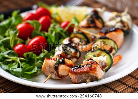 Fish skewers with salad - stock photo