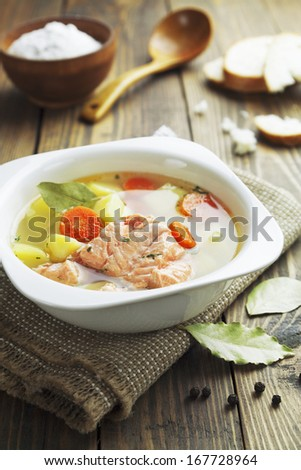 Fish soup in a square bowl on the table - stock photo