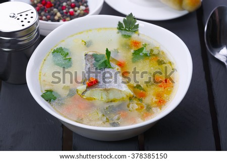 Fish soup on wooden table.