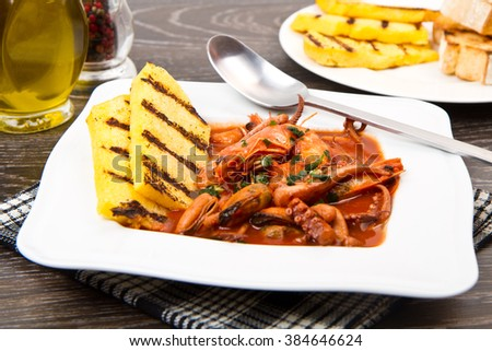 fish soup with grilled polenta on white dish - stock photo