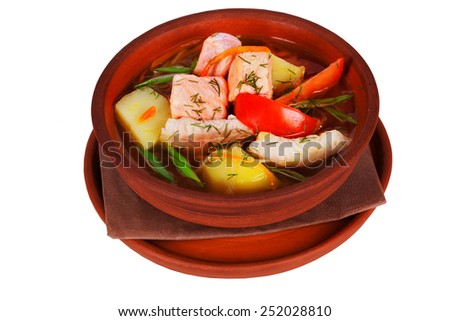 fish soup with red and white fish, potatoes and vegetables in a pot on a white background for the menu - stock photo