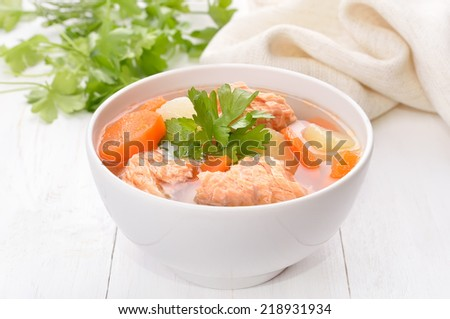 Fish soup with salmon in bowl on white wooden table - stock photo