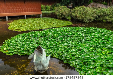 Fish statue in a japanese style garden. - stock photo
