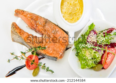 fish steak with vegetables on white plate