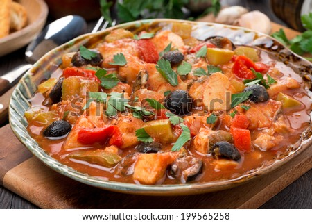 fish stew in tomato sauce on a plate, close-up