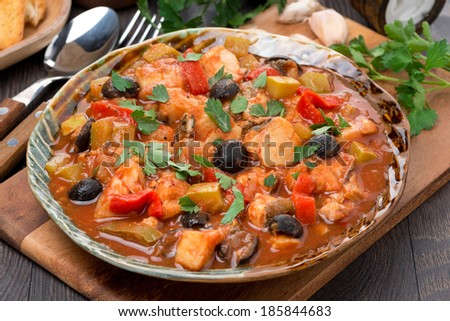 Fish stew with olives in tomato sauce on a plate, horizontal