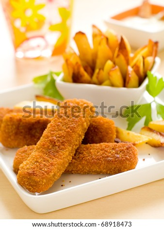 Fish sticks and fried potatoes with sauce on plate