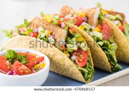 Fish tacos shell with tomato, beans, capsicum and avocado salsa